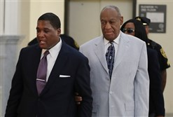 Bill Cosby, right, is led into Courtroom A in the Montgomery County Courthouse by one of his aides, on Tuesday.