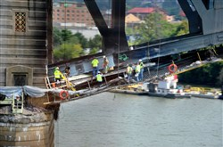 Workers reinforce a steel beam damaged in Friday's tarp fire.