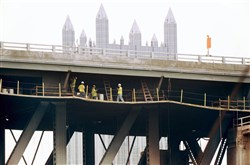 A crew works on the Liberty Bridge on Thursday, six days after the fire occurred.