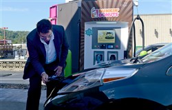 Rock Henderson, with GoSpace, unhooks a Nissan LEAF from the charging station at Dunkin Donuts on Foster Avenue in Crafton.