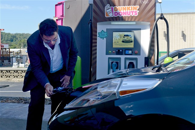 Rock Henderson, of GoSpace, the installation company for electric vehicle charging stations, unhooks a Nissan LEAF from the newly installed charging station at Dunkin' Donuts on Foster Avenue in Crafton during the grand opening of 50kW charging stations in seven locations in the Pittsburgh area last week.