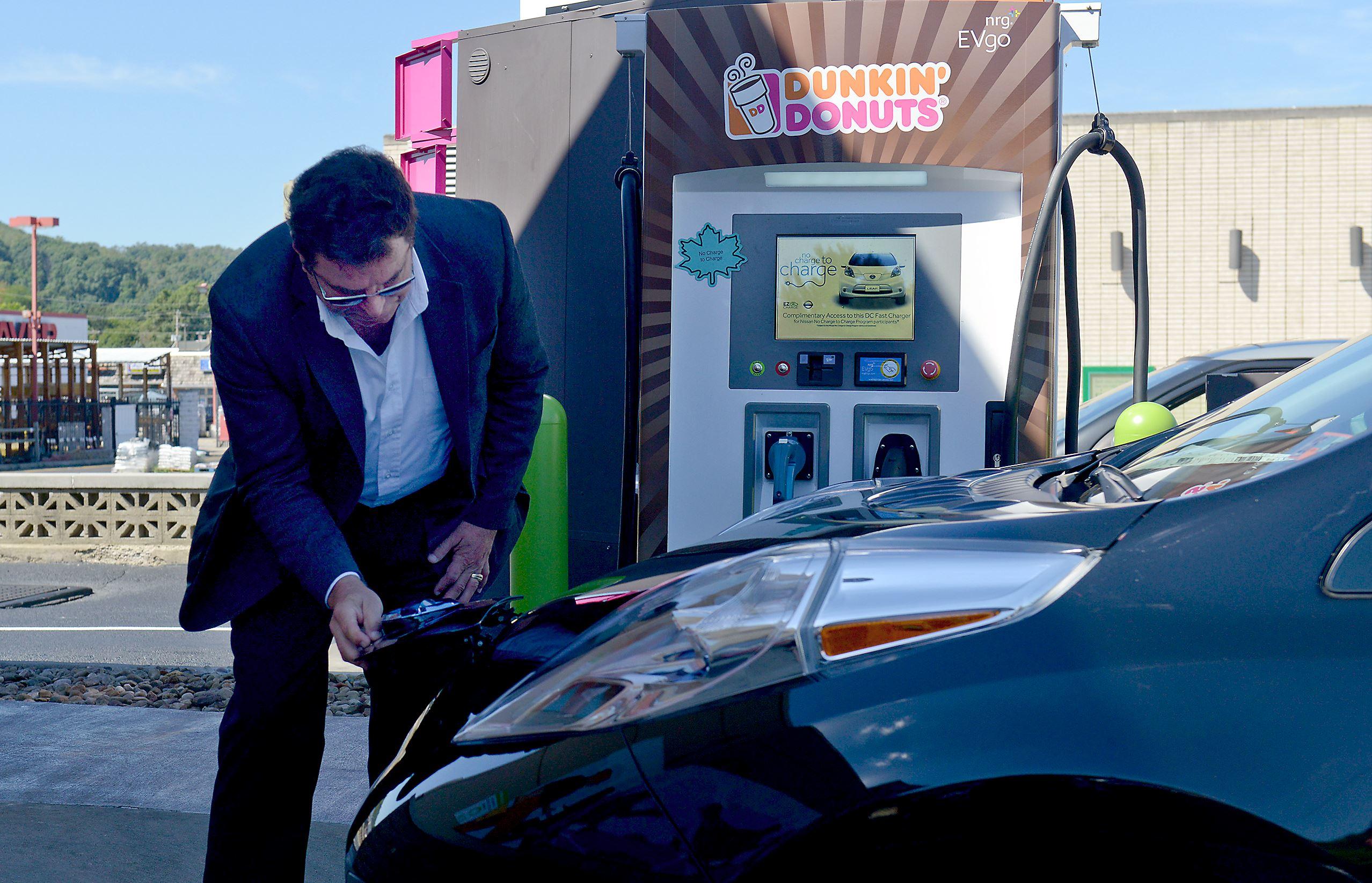 20160913ppDunkinCharge1BIZ Rock Henderson, with GoSpace, unhooks a Nissan LEAF from the charging station at Dunkin Donuts on Foster Avenue in Crafton.