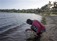 Jalia skims the water with her fingers during an evening outing to Lake Victoria. She was orphaned when both of her parents died of AIDS. Her goal is to become a surgeon.