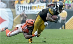 The Steelers' DeAngelo Williams carries for a first down as he's defended by Bengals' Shawn Williams in the fourth quarter Sunday at Heinz Field.