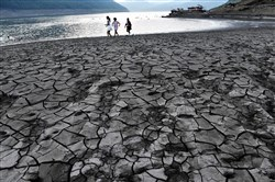 This file photo taken Aug. 24 shows people walking along the dried and cracked river beach of the Yangtze River in Yunyang county in Chongqing.