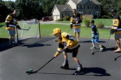 Jacob Lestitian, 10, and his brother Matthew, 8, get a chance to play street hockey with Penguins players from left, Tom Kuhnhackl, Bryan Rust and Conor Sheary.