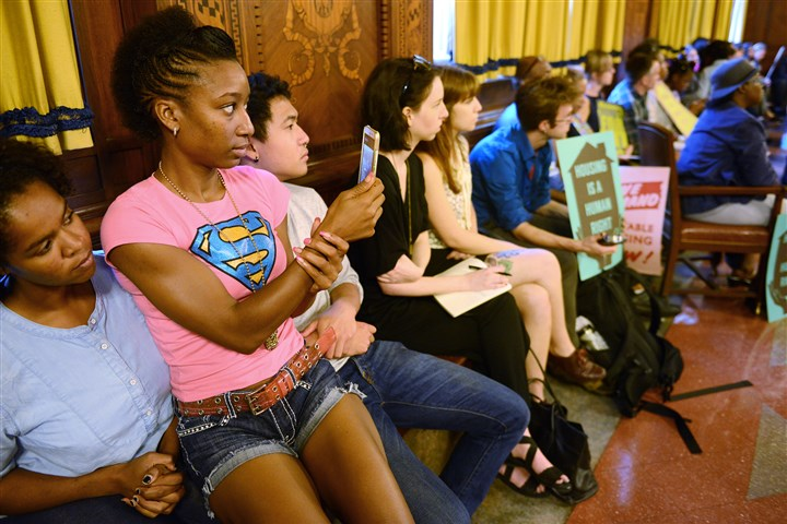 20160921rldAffordableHousing01 Rashelle Heggins, center, of Homewood sits on the laps of her friends Fatema Juma, 21, of Greenfield and Kai Pang of North Oakland as she records video during a public hearing Wedensday at the City-County Building, Downtown.