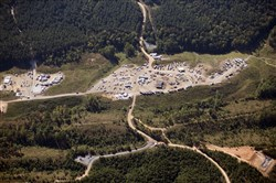 In this aerial photo, a response team works to clean a pipeline gas leak Tuesday near Helena, Ala. A main gas line is expected to restart Wednesday with a temporary bypass after a leak and spill in Alabama led to surging fuel prices and some gas shortages across the South, a Colonial Pipeline official said Tuesday. (AP Photo/Brynn Anderson)