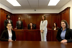 Elizabeth DeLosa, in white, managing attorney for the Pennsylvania Innocence Project's Pittsburgh office, stands along with, from left, law students Jennifer Vogel, seated, from Duquesne University; Sean Champagne, University of Pittsburgh; Kyle Watson, Pitt; Kelsey Ayers, Duquesne; Kristi Heidel, Duquesne; and Susannah Glick, Duquesne, inside a classroom in the Duquesne University Tribone Center for Clinical Legal Education in Uptown.