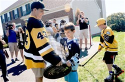 The Penguins' Conor Sheary helps Matthew Lestitian, 8, lift the Stanley Cup on Wednesday outside Matthew's home in Mars. Penguins players were delivering season tickets to Matthew's dad, Kevin Lestitian.