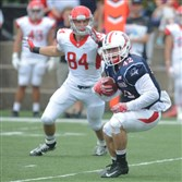 Duquesne linebacker Carter Henderson intercepts a pass last week against Dayton, which he returned 23 yards for a touchdown in the third quarter.