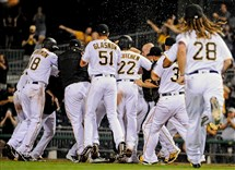 Water and sunflower seeds fly through the air as the Pirates celebrate their walk-off win against the Washington Nationals at PNC Park in North Side on Friday.