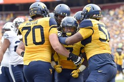 West Virginia running back Rushel Shell, center, celebrates his touchdown with offensive linemen Tony Matteo, left, and Adam Pankey, right, during the first half Saturday against BYU in Landover, Md.