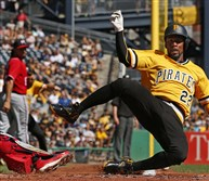 The Pirates' Andrew McCutchen scores from third on a throw down to second base by Washington Nationals catcher Jose Lobaton in the first inning.