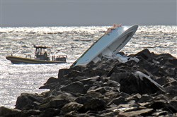 The boat Jose Fernandez was riding in lies overturned on a jetty Sunday off Miami Beach, Fla.