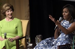 "First lady Michelle Obama, accompanied by former first lady Laura Bush, speaks during the ""America's First Ladies: In Service to Our Nation"" conference at the National Archives in Washington, D.C., on Friday."
