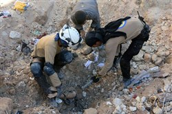 Members of Civil Defense removing a dead body Saturday from under the rubble after airstrikes hit in Aleppo, Syria.