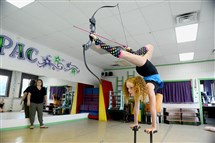 Bella Gantt, a 10-year-old from Greensburg, Pa., practices the part of her contortionist routine where she fires a bow and arrow with her feet, as Betsy Shuttleworth, the owner of Dance Extensions Performing Arts Center in Canonsburg, watches.