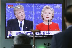 People watch the U.S. presidential debate between Hillary Clinton and Donald Trump at Seoul Railway Station in Seoul, South Korea.