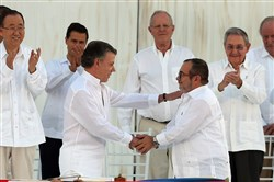 Colombia's President Juan Manuel Santos, front left, and the top commander of the Revolutionary Armed Forces of Colombia (FARC) Rodrigo Londono, known by the alias Timochenko, shake hands Monday after signing the peace agreement between Colombia's government and the FARC to end over 50 years of conflict in Cartagena, Colombia.