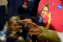A woman wears a shirt depicting Hillary Clinton as Rosie the Riveter as people gather to watch Michelle Obama speak on behalf of the Democratic presidential candidate on Wednesday at the Fitzgerald Field House on the University of Pittsburgh campus in Oakland.