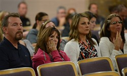 Community members listen as Plum School Board officials discuss whether to reinstate superintendent Timothy Glasspool during a meeting Tuesday night. The board approved the move.