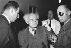 A photo from the Israel Defense Forces and Defense Ministry Archives showing, in foreground from left, Israeli statesmen Shimon Peres, David Ben-Gurion and Moshe Dayan