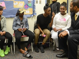 """University Prep principal Christopher Horne speaks with students during a """"Girls Circle,"""" a structured group designed to encourage girls to share experiences that are helpful to one another in September."""
