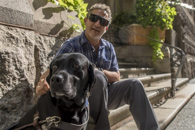 Brian Jakubowski and his seeing-eye dog, Darla, outside the Allegheny County Courthouse, Downtown, where Mr. Jackubowski works.