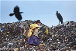 Ragpickers search for reusable material Saturday at a garbage dumping site on the outskirts of Gauhati, India. India deposited ratification instruments of the Paris Agreement on Sunday.