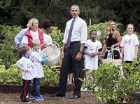 Bruce Allen, a fifth-grader at Pathways K-5 Charter School, Downtown, stands behind President Barack Obama as he helped harvest produce in the White House Kitchen Garden in October 2016. Carrying a basket at back right is singer Ashanti.