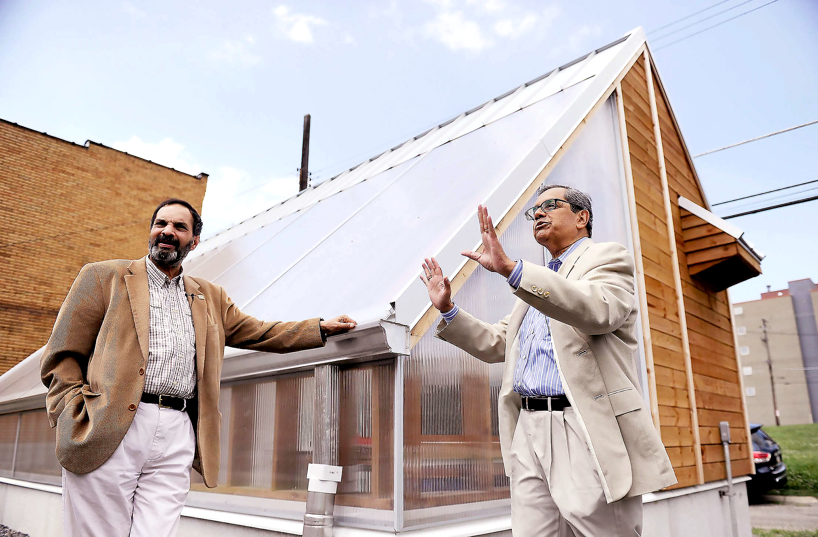 BULLDOG - 20160708MWHIndiaAdvance01 University of Pittsburgh professors Bopaya Bidanda, left, and John Camillus, right, in July 2016. They described their vision for a solar-powered microgrid in Homewood while showing off the first piece: a bioshelter powered by a canopy of solar panels next to the Bible Center Church, Inc. on Fleury Way.
