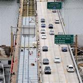 Traffic slowly moves along the Liberty Bridge while construction workers rebuild the deck of the span.