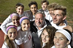 Freedom's Colin Williams, surrounded by his players, coaches both the boys and girls soccer teams.