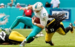 Dolphins quarterback Ryan Tannehill is tackled by linebacker Jarvis Jones Sunday at  Hard Rock Stadium in Miami Gardens, Fla.