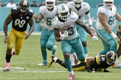 Dolphins' Jay Ajayi carries in front of Steelers' Ross Cockrell in the third quarter Sunday at Hard Rock Stadium.