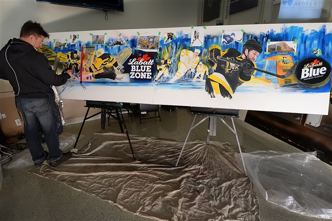 Sports artist David Arrigo creates mural showcasing the Penguins iconic jersey and other Pittsburgh landmarks at the PPG Paints Arena.