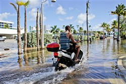 A motorbike navigates through floodwater caused by a seasonal king tide in Hollywood, Fla. this past fall.