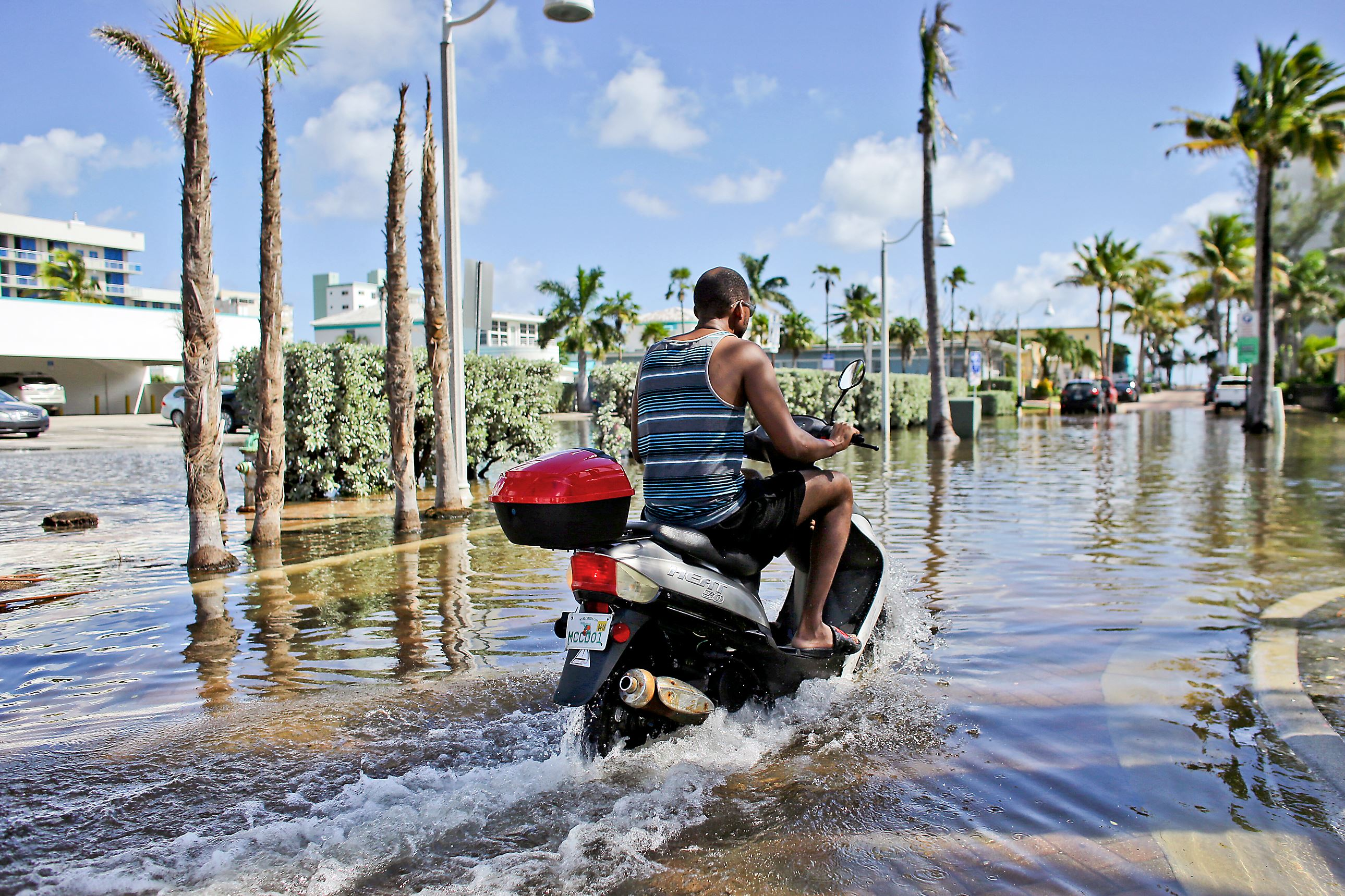 Florida-King-Tide-JPEG-4786-1 A motorbike navigates through floodwater caused by a seasonal king tide in Hollywood, Fla. this past fall.