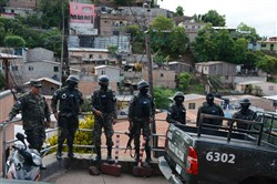 Members of the Criminal Investigation Technical Agency and the Military Police take part in the second phase of Operation Avalanche aimed at seizing property and arresting leaders of the MS-13 criminal gang in Tegucigalpa, Honduras, on Monday.