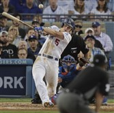 The Los Angeles Dodgers' Corey Seager hits an RBI single in the third inning Tuesday night of Game 3 of the National League Championship Series against the Chicago Cubs at Dodger Stadium.