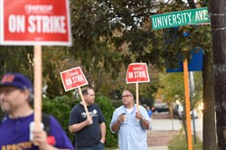 West Chester University professors Chris Stangl, left, and John Elmore carry picket signs as they and other faculty in the Pennsylvania State System of Higher Education went on strike Wednesday morning.
