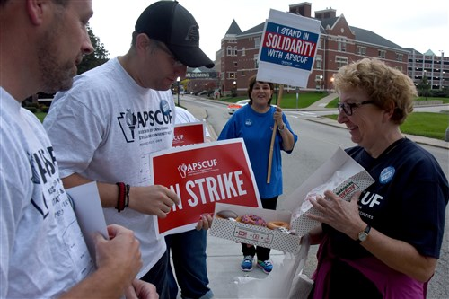 Cerenna Sealy passes out doughnuts to picketing members of APSCUF on Wednesday along Third Street near the entrance of California University of Pa.