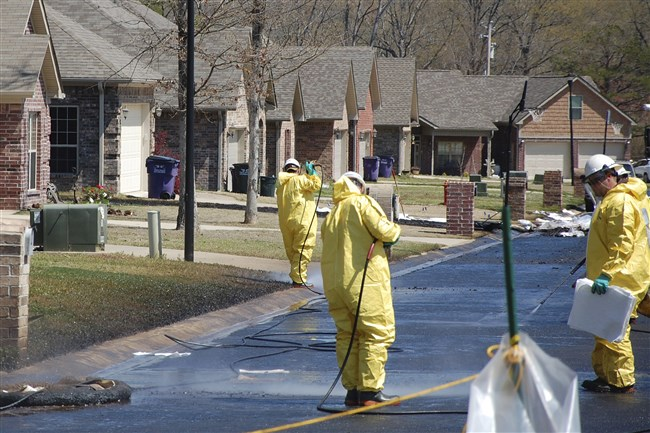 In this April 1, 2013 file photo, crews work to clean up oil in a Mayflower, Ark., neighborhood after an oil pipeline ruptured and spewed oil over lawns and roadways. Attorneys for landowners along the crude oil pipeline that ruptured in 2013 are asking a federal appeals court to reinstate their case. Landowners sued Exxon Mobil Pipeline Co., in 2013, alleging a breach of contract, but the case was dismissed in 2015. Oral arguments will be held Wednesday, Oct. 19, 2016, in Minnesota.