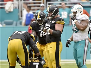 Teammates help Steelers quarterback Ben Roethlisberger to his feet after taking a hit from Dolphins' Ndamukong Suh (right) late in the fourth quarter Sunday.