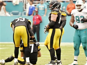 Teammates help Steelers quarterback Ben Roethlisberger to his feet after taking a hit from Dolphins' Ndamukong Suh late in the fourth quarter Sunday.