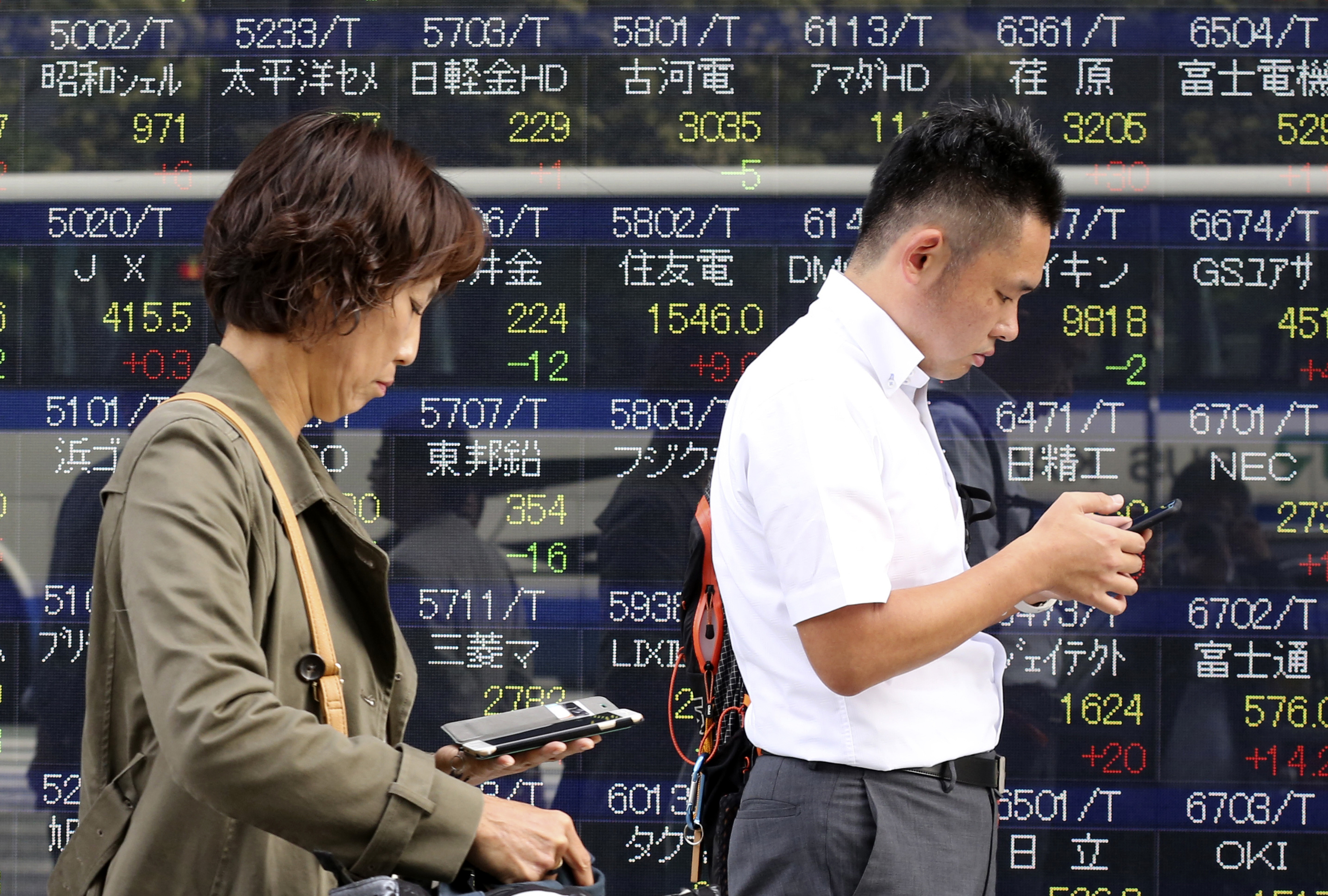 Japan Financial Markets-1 People look at their mobile phone at an electronic stock board of a securities firm in Tokyo Friday Oct. 21 2016. Asia stock markets drifted Friday as oil prices slid. The dollar rallied after Europe's central bank kept