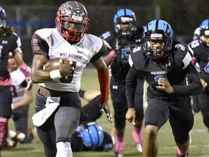 West Allegheny's Kenny White carries for a touchdown against Woodland Hills Friday night at Wolvarena in Turtle Creek.