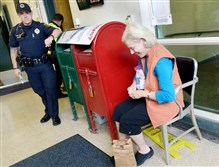 Marcia Swartz of Squirrel Hill talks to Patrolman Brian Markus as she dumps unwanted prescription pills into a paper bag Saturday at the Zone 4 police station in Squirrel Hill on National Prescription Drug Take Back Day.