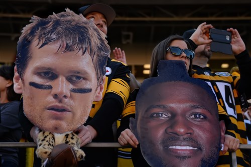 Steelers fans hold up cutout heads before the game.
